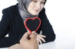 Романтичная рука взгляда держа символ сердца сделанный от древесины над запачканной предпосылкой Стоковая Фотография RF