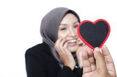 Романтичная рука взгляда держа символ сердца сделанный от древесины над запачканной предпосылкой Стоковые Изображения