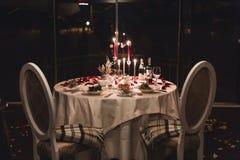 Романтичная сервировка стола с вином, красивыми цветками в коробке, пустыми стеклами, лепестками розы и свечами стоковая фотография rf