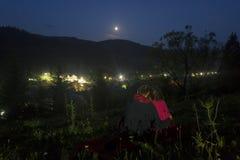Романтичная сцена пар наблюдая лунная или затмения луны стоковые изображения rf