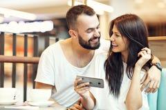 Романтичное датировка пар в кафе и smartphone использования стоковое фото rf