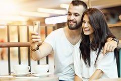 Романтичное датировка пар в кафе и smartphone использования стоковое изображение rf