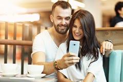 Романтичное датировка пар в кафе и smartphone использования стоковое изображение