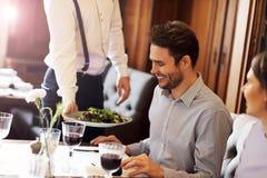Романтичное датировка пар в ресторане будучи послуженным кельнером стоковая фотография rf