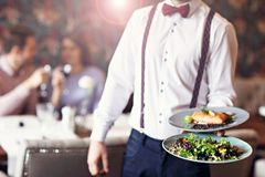Романтичное датировка пар в ресторане будучи послуженным кельнером стоковые изображения