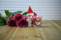 Романтичное изображение фотографии сезона зимы рождества с красными розами и освещенной свечой с украшением снеговика зефира Стоковые Изображения