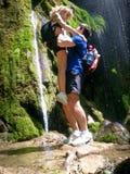Романтичное изображение, человек подняло вверх женщину около водопада леса Стоковое Фото