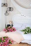 Романтичное утро в шикарной спальне Большой букет розовых тюльпанов лежит на белой кровати Классический дизайн спальни Стена кирп стоковое изображение rf