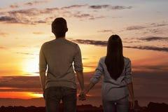 Романтичные азиатские пары держа руки смотря заход солнца Стоковые Фото