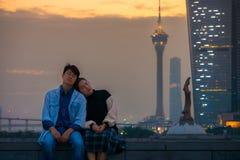 Романтичные азиатские пары сидя рядом с Kun я конвенция башни статуи и Макао Стоковые Фото