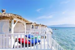 Романтичные деревянные бунгала салона с sunbeds ротанга на море Стоковые Изображения RF