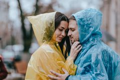 Романтичные любящие пары, парень и его девушка в плащах стоят лицом к лицу на улице в дожде стоковое изображение