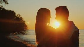Романтичные многонациональные пары обнимая на заходе солнца, стоя против моря Смотреть один другого стоковая фотография rf