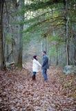 Романтичные молодые пары держа руки идя в древесины стоковые изображения