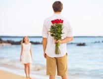 Романтичные молодые пары в влюбленности, букет сюрприза удерживания человека r стоковые изображения