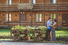 Романтичные молодые пары обнимая один другого около декоративные деревянные тележки с цветками, на предпосылке деревенского стиля Стоковая Фотография