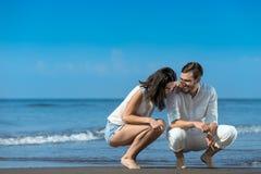 Романтичные молодые пары рисуют формы в песке пока на медовом месяце Стоковая Фотография RF