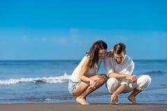 Романтичные молодые пары рисуют формы в песке пока на медовом месяце Стоковые Фотографии RF