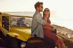 Романтичные молодые пары сидя на клобуке их автомобиля Стоковое фото RF