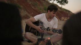 Романтичные молодые пары сидя огнем на пляже вместе с друзьями Человек играет гитару и женщину акции видеоматериалы