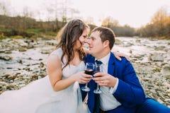 Романтичные молодые bridal пары выпивая вина на речном береге камешка с холмами и потока как предпосылка Стоковые Фотографии RF