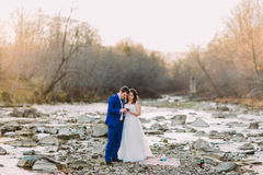 Романтичные молодые bridal пары выпивая вина на скалистом речном береге камешка с Forest Hills и потоком Стоковое Изображение