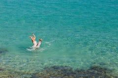 Романтичные нов-пожененные пары наслаждаясь летними каникулами Детеныши холят поднимать его невесту в море Стоковое Изображение RF