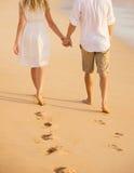 Романтичные пары держа руки идя на пляж на заходе солнца Стоковые Изображения