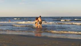 Романтичные пары играя и дразня одно другое в море на пляже акции видеоматериалы