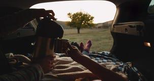 Романтичные пары имеют полезного время работы совместно на пикнике они лежа в багажнике автомобиля и носить уютные носки использу сток-видео