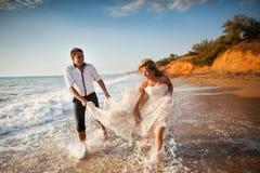 Романтичные пары имея потеху на пляже Детеныши в влюбленности, привлекательном человеке и женщине наслаждающся выравниваться, дер Стоковое Изображение
