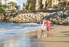 Романтичные пары идя вдоль пляжа на заходе солнца Стоковое Фото