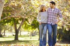 Романтичные пары идя через полесье осени Стоковые Изображения