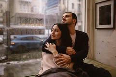 Романтичные пары Любя парень обнимает его красивую девушку сидя на windowsill в уютном кафе стоковое изображение