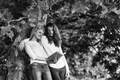 Романтичные пары 2 маленькой девочки прочитали книгу Стоковые Изображения RF