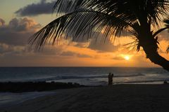 Романтичные пары на пляже с заходом солнца Стоковое Изображение RF