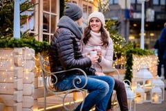 Романтичные пары нося теплые одежды сидя на стенде в выравнивать улицу украшенную с красивыми светами, говоря и стоковое фото rf