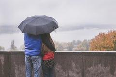 Романтичные пары обнимая в улице стоя под зонтиком Стоковая Фотография RF