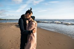 Романтичные пары обнимая на пляже на заходе солнца Мягкие солнечные цветы Холодная погода осени стоковое фото rf