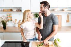 Романтичные пары подготавливая обедающий в кухне дома Стоковое Фото