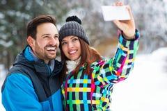 Романтичные пары принимая selfie снега Стоковое Фото