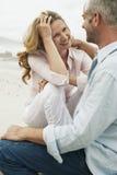 Романтичные пары сидя на пляже стоковая фотография