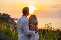 Романтичные пары смотря заход солнца Стоковое Фото
