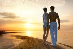 Романтичные пары смотря заход солнца Стоковая Фотография RF