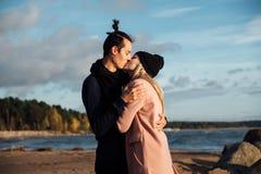 Романтичные пары целуя и обнимая на пляже на заходе солнца Мягкие солнечные цветы Холодная погода осени, деревья на заднем плане стоковое изображение rf