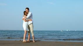 Романтичные пары целуя на пляже на море видеоматериал