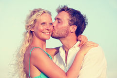 Романтичные пары целуя наслаждающся заходом солнца на пляже Стоковые Фотографии RF