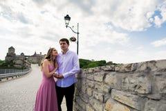 Романтичные пары человека и женщины на мосте с старым замком на заднем плане Стоковые Изображения
