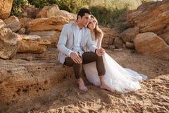 Романтичные пожененные пары сидя на пляже Стоковое Изображение RF