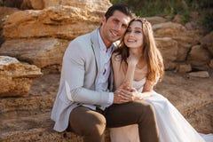 Романтичные пожененные пары сидя на пляже Стоковое Изображение